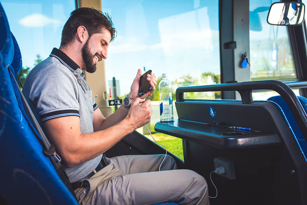 passenger on bus with phone and outlet